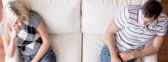 couple sitting far apart on couch
